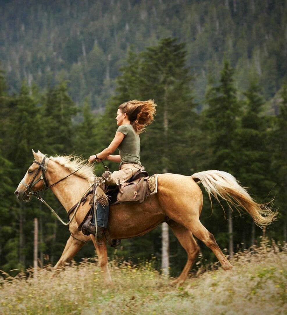Woman horseback riding in the mountains- PEMF Health Inc.